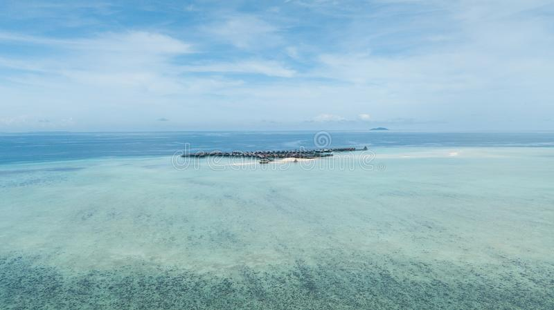 Drone view of a resort over a reef surrounded by clear water royalty free stock image