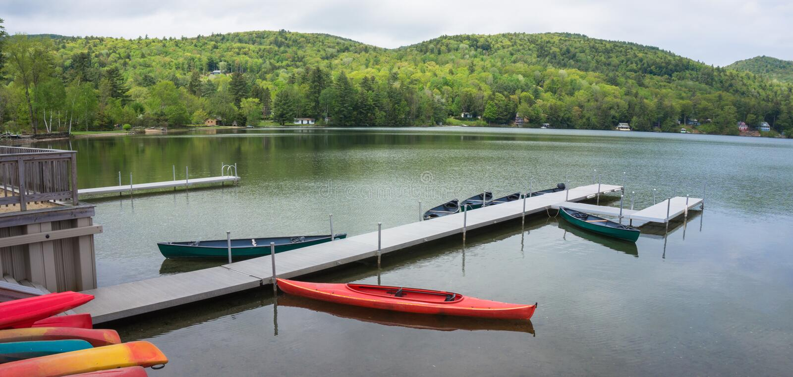 Resort pier on lake. Pier from resort with kayaks and canoes ready for water sport enjoyment royalty free stock images