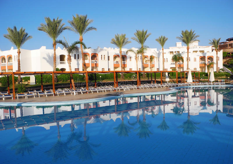 Resort in Sharm El Sheikh. Sharm El Sheikh, Egypt - August 25, 2016: Swimming pool and palm trees at the resort in Sharm El Sheikh stock photography