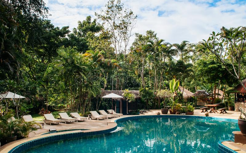 Resort style beach daybeds and umbrellas by swiming pool in tropical garden, Kanchanaburi, Thailand royalty free stock image
