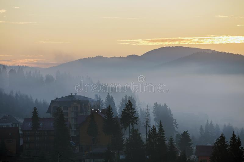 Resort village houses buildings on background of foggy blue mountain hills covered with dense misty spruce forest under bright royalty free stock photos