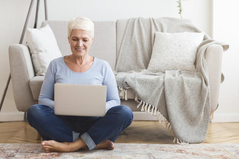 Resourceful mature woman sitting on floor and using laptop. Resourceful mature smiling woman sitting on floor and using laptop at home, copy space stock images