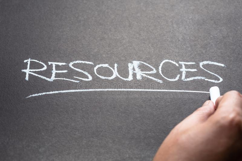 Resources on Chalkboard. Closeup hand write a topic RESOURCES on chalkboard royalty free stock photos