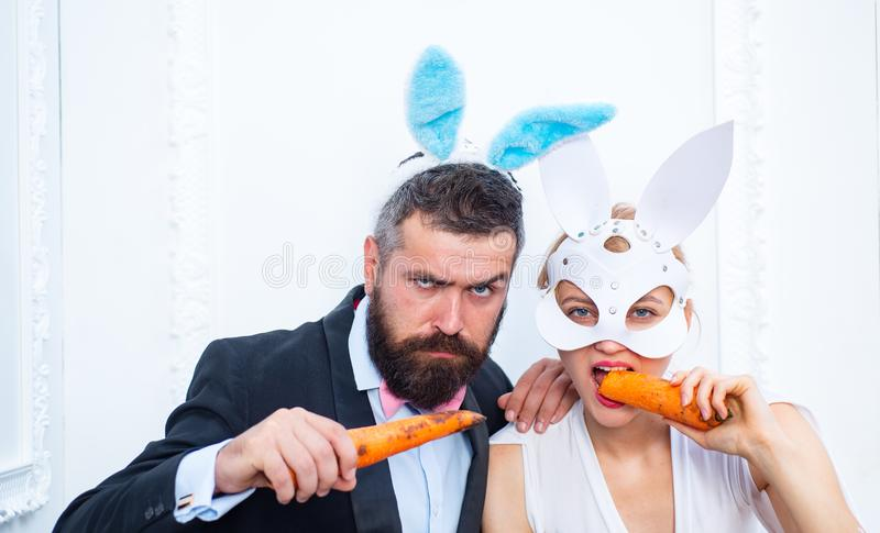Respect traditions. Happy easter day. Bunny rabbit man and girl eat carrot. Cute bunny wear formal suit tuxedo royalty free stock photo