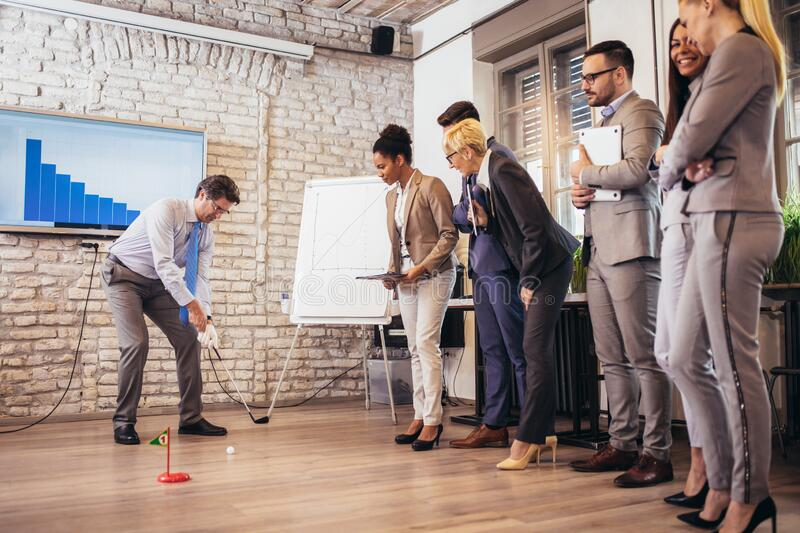 Elderly man in a business suit playing mini-golf in his office. Nearby are his assistants and watching. Respectable elderly men in a business suit playing mini royalty free stock photo