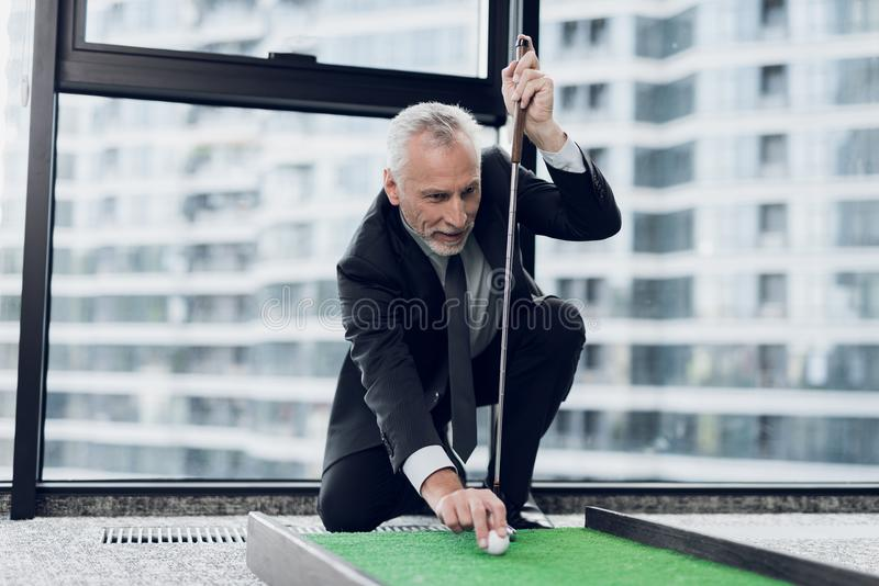 A respectable elderly man playing a mini golf in the office. He puts the ball before the blow stock image