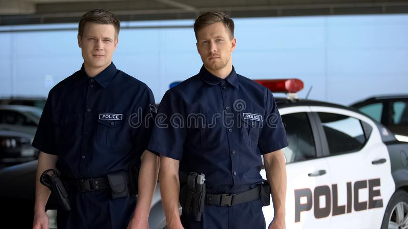 Respectable policemen standing against squad car on background, important job. Stock photo stock photography