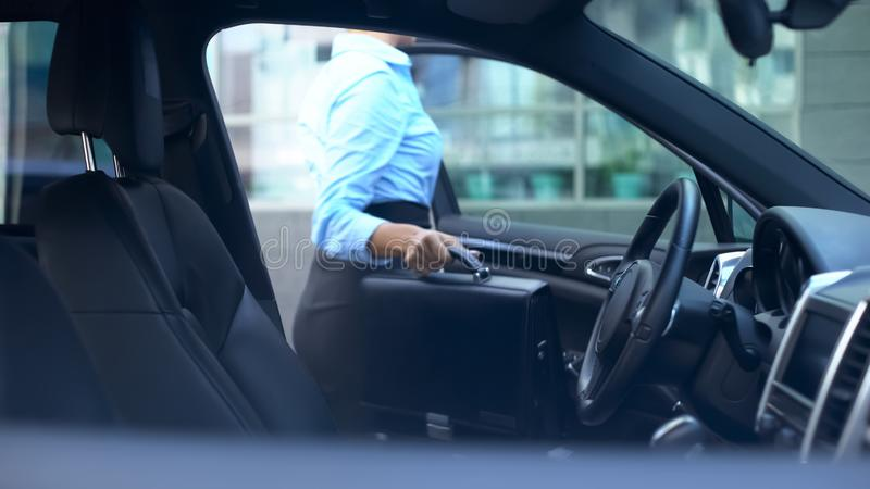 Respectable woman gets out of car parked near office center, busy lifestyle stock photo