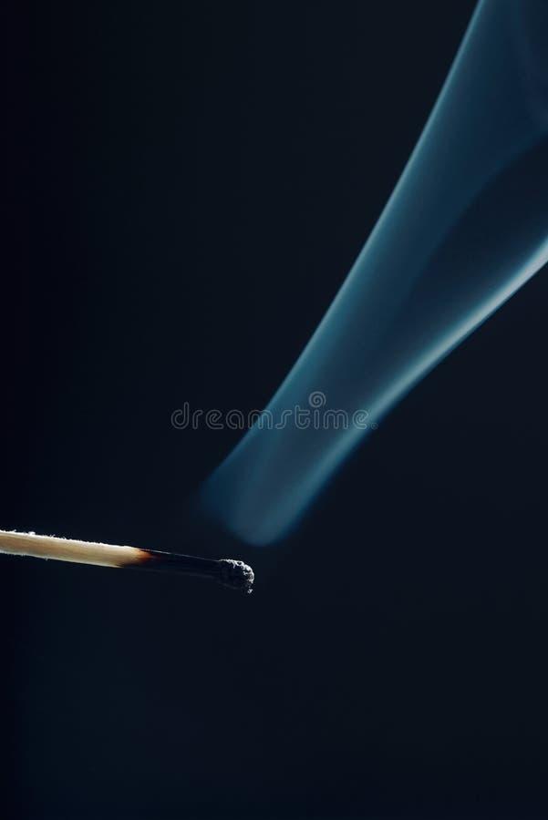 Respecter le bâton avec la tête brûlée et fumer autour photos libres de droits
