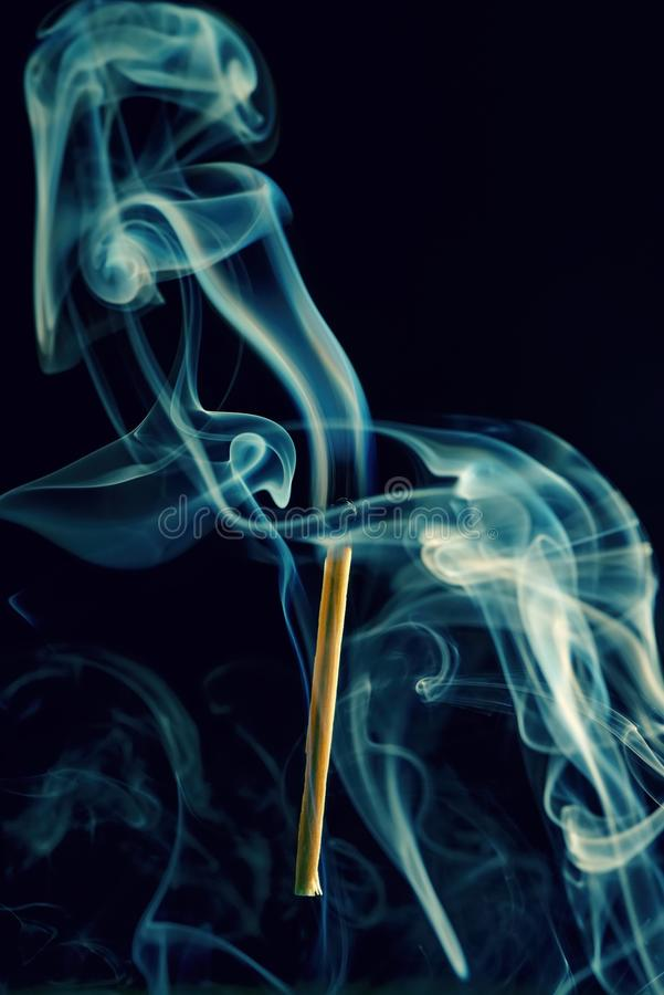 Respecter le bâton avec la tête brûlée et fumer autour photographie stock libre de droits
