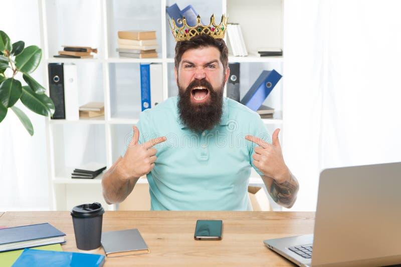 Respectez-moi Le patron grossier arrogant d'homme avec la couronne d'or s'asseyent dans le bureau La confiance en soi de supérior photographie stock