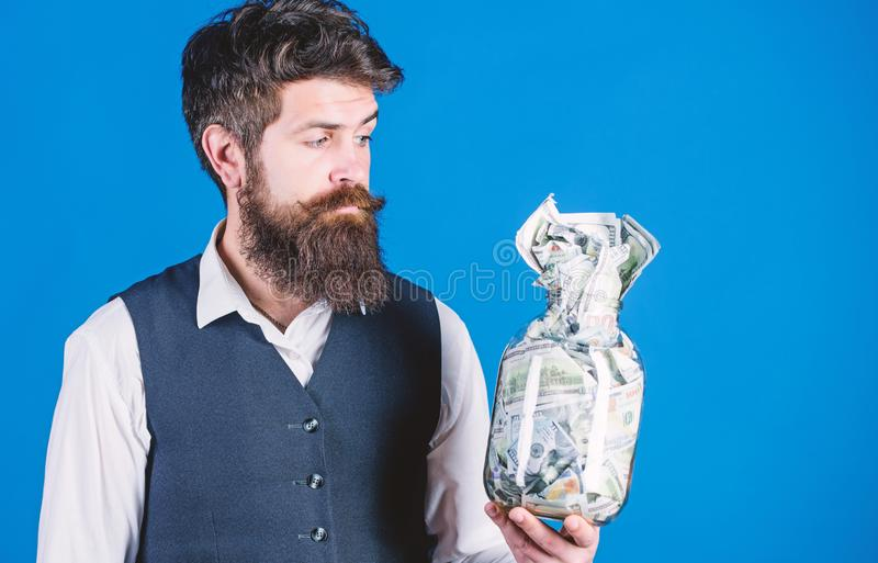 He respects money. Bearded man keeping money in glass jar. Hipster holding jar with american money. Saving money in cash stock image