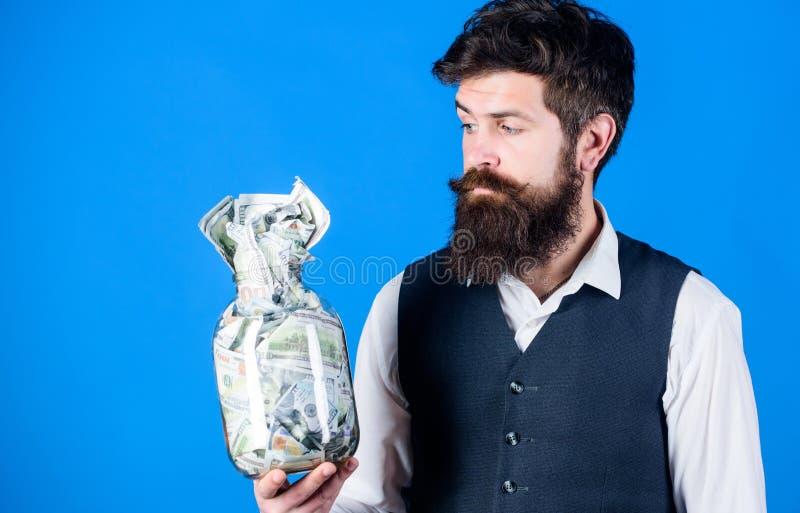 Respeita o dinheiro Homem farpado que mantém o dinheiro no frasco de vidro Frasco da terra arrendada do moderno com dinheiro amer imagem de stock