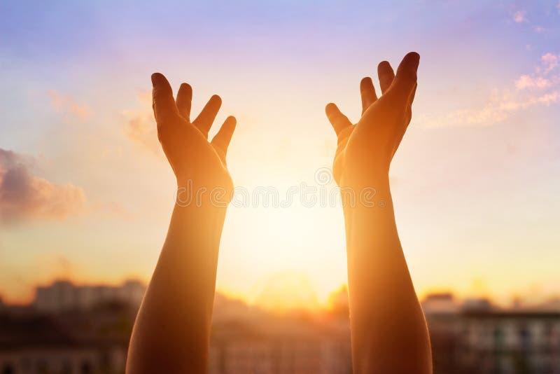 Respektera och be på solnedgången i stadsbakgrund fotografering för bildbyråer