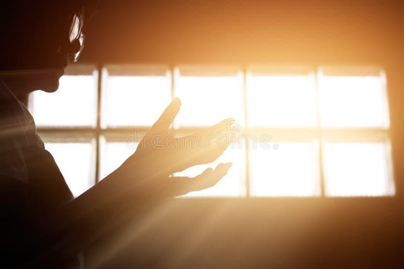 Respete y ruegue en el cuarto con salida del sol a través de fondo de la ventana fotos de archivo