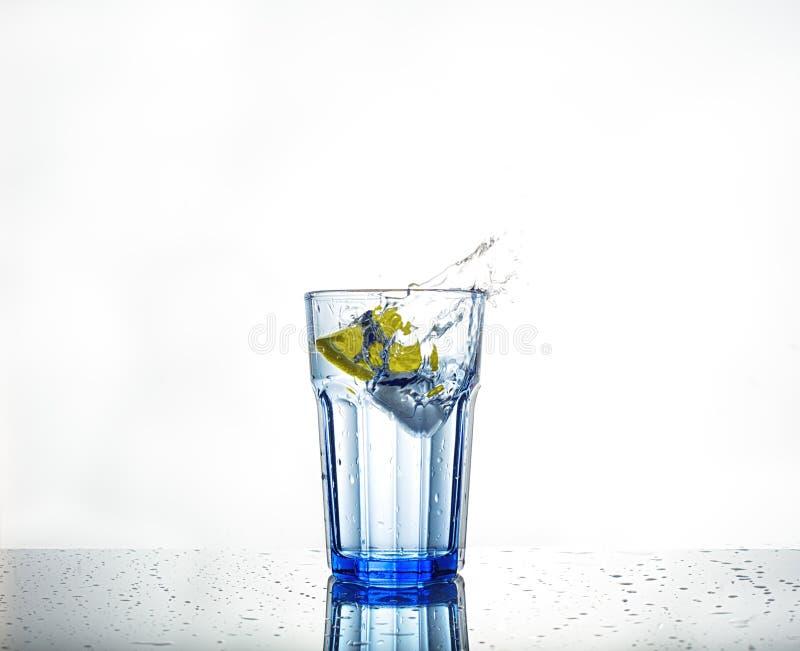 Respingo da água com gelo e limão em um vidro fotografia de stock royalty free