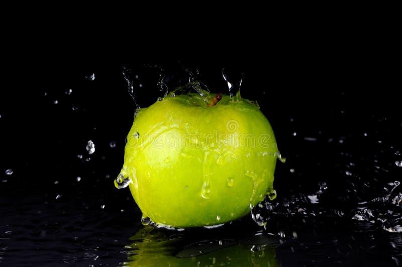 Respingo da água fresca na maçã verde fotografia de stock