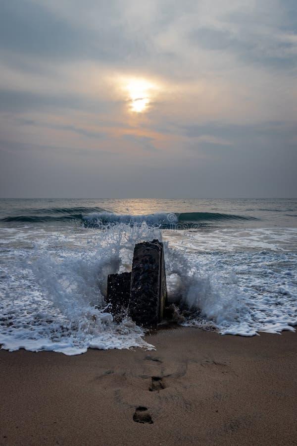 Respingo da água na rocha da praia com opinião do nascer do sol foto de stock royalty free