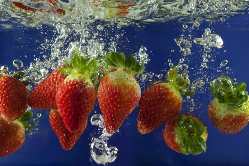 Respingo da morango na água com bolhas fotos de stock royalty free