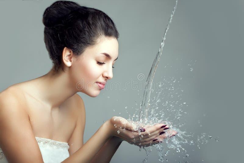 Respingo da mulher e da água Gotas e bolhas da água nas mãos das meninas imagem de stock