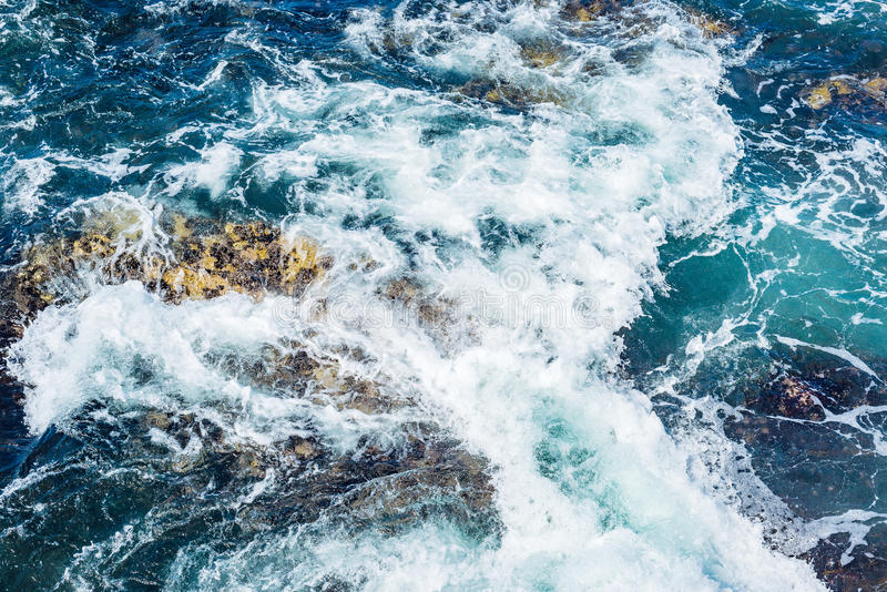 Respingo da onda do mar do oceano na costa rochosa, lote da espuma e obscuridade - água azul fotografia de stock