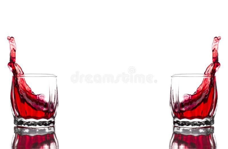 Respingo do suco vermelho, vinho em um vidro com nervuras de vidro do uísque em um fundo branco fotografia de stock royalty free