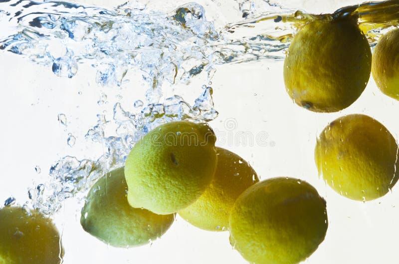 Respingo dos limões na água imagens de stock royalty free