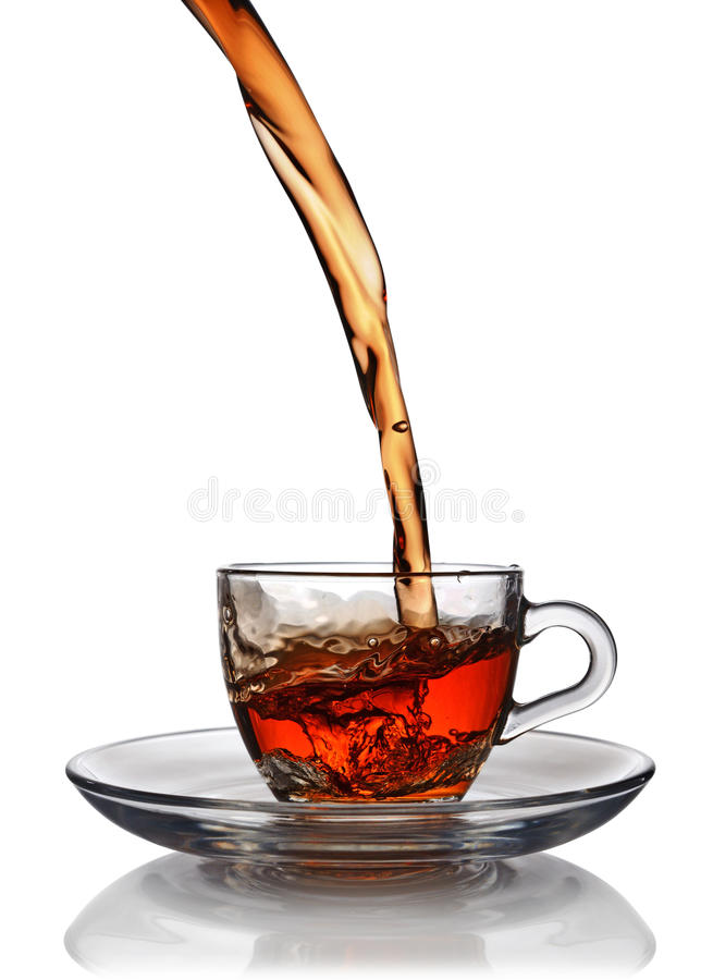Respingo no copo de vidro do chá preto fotos de stock royalty free