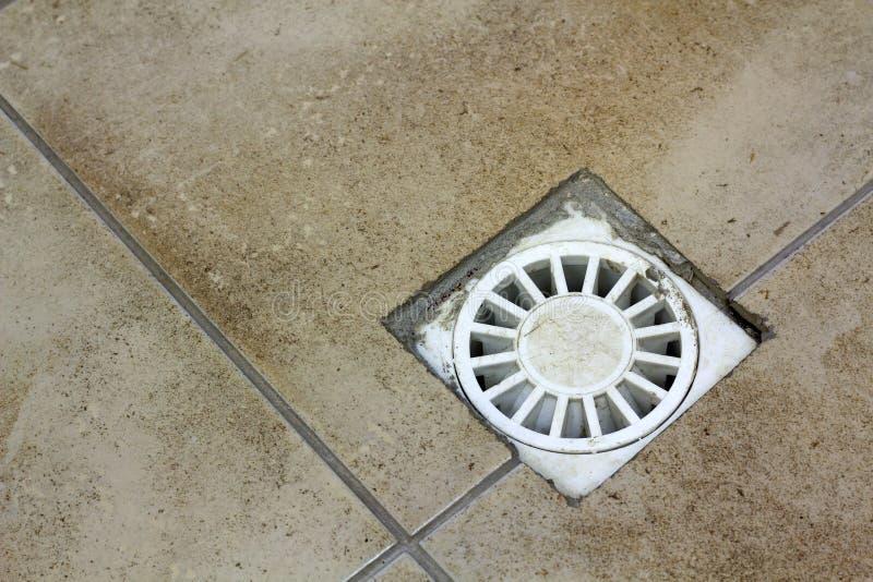 Respiradouro do dreno da água no assoalho velho telhado cerâmico do vintage da cozinha, do banheiro ou do porão Fundo bege abstra fotografia de stock royalty free