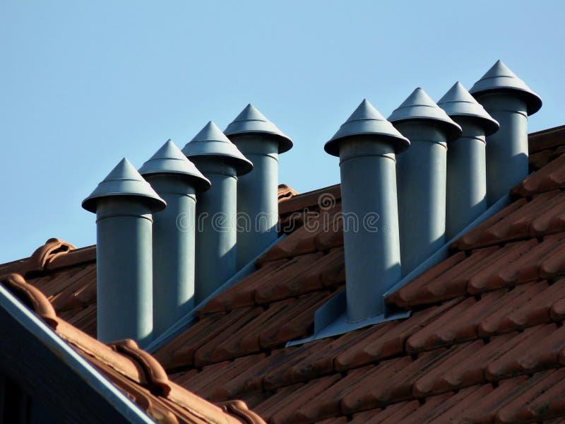 respiradouros pointy do telhado do metal no telhado de telha inclinado da argila na luz do dia brilhante com céu azul fotografia de stock royalty free