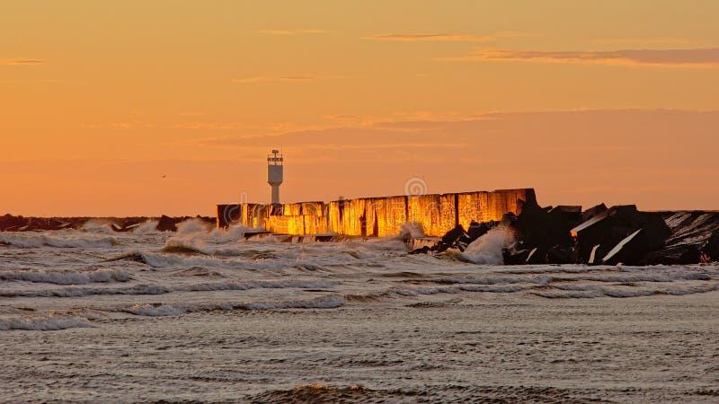 Resplandor anaranjado y ondas de la puesta del sol que salpican contra el rompeolas en el mar Báltico imagen de archivo