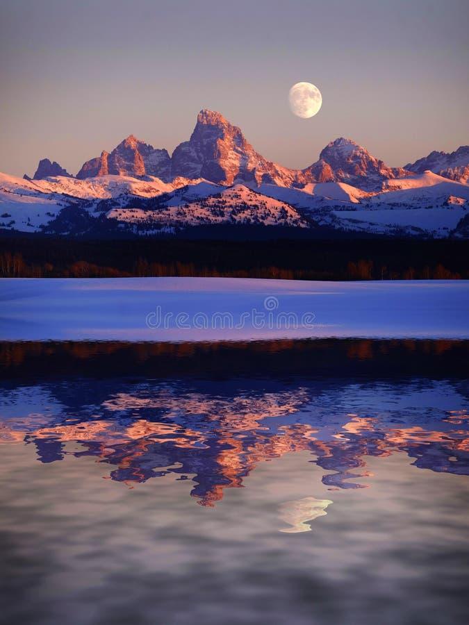 Resplandor de Alpen de la luz de la puesta del sol en las montañas de Tetons Teton con la luna que sube para reflejar el lago de  foto de archivo