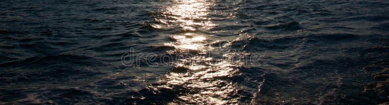Resplandor de la puesta del sol en el agua imagenes de archivo