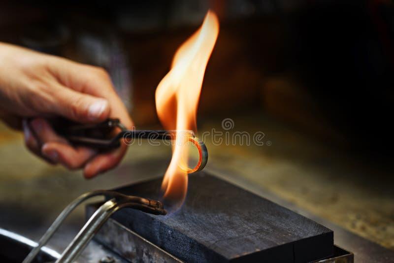Resplandor de las manos del orfebre un anillo de oro en una llama del gas, cierre para arriba con imagenes de archivo