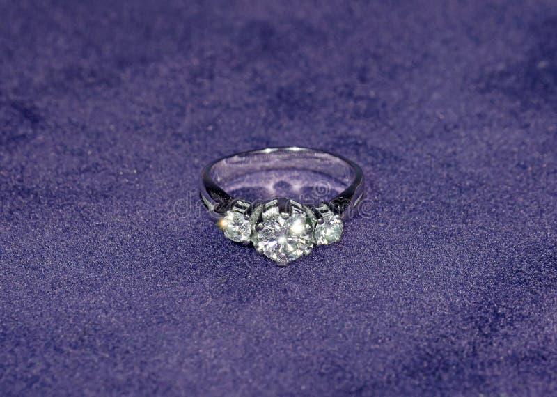 Resplandor Diamond Ring de plata en Violet Velvet Background imagenes de archivo