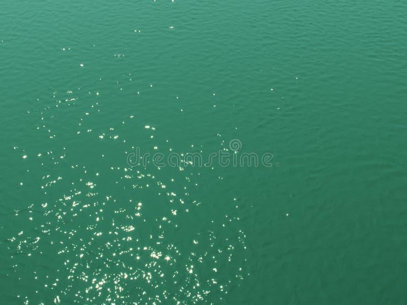 Resplandores chispeantes solares brillantes brillantes en la superficie profunda turquesa-verde brillante del lago, fondo fotos de archivo