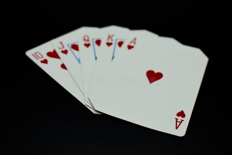 Resplendor reto de resplendor real de cartões dos corações no jogo de pôquer contra o fundo preto imagem de stock royalty free