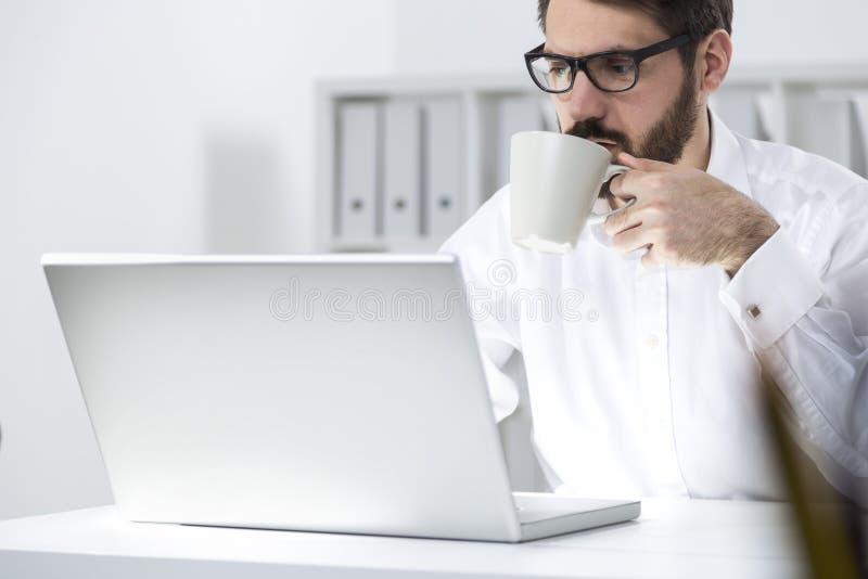 Responsabile che mangia caffè in ufficio fotografie stock