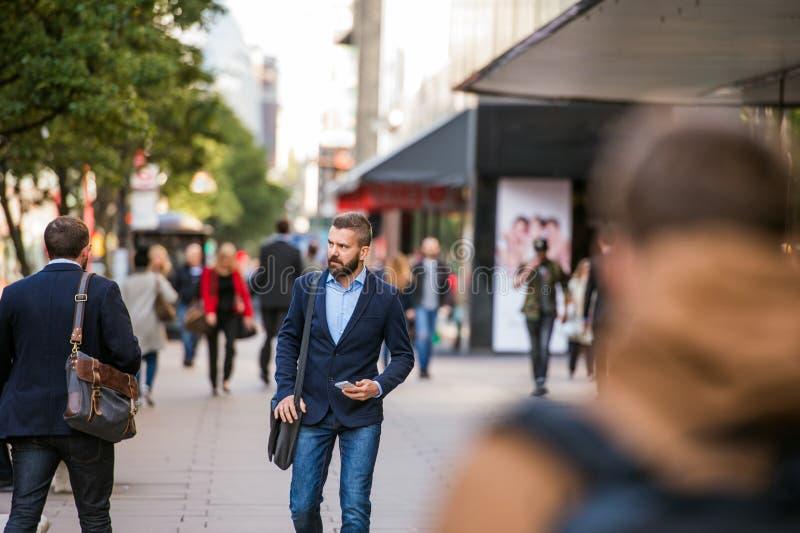 Responsabile dei pantaloni a vita bassa con lo Smart Phone che cammina nella via fotografia stock