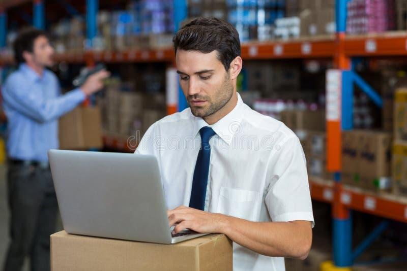 Responsabile del magazzino che lavora al computer portatile fotografia stock libera da diritti