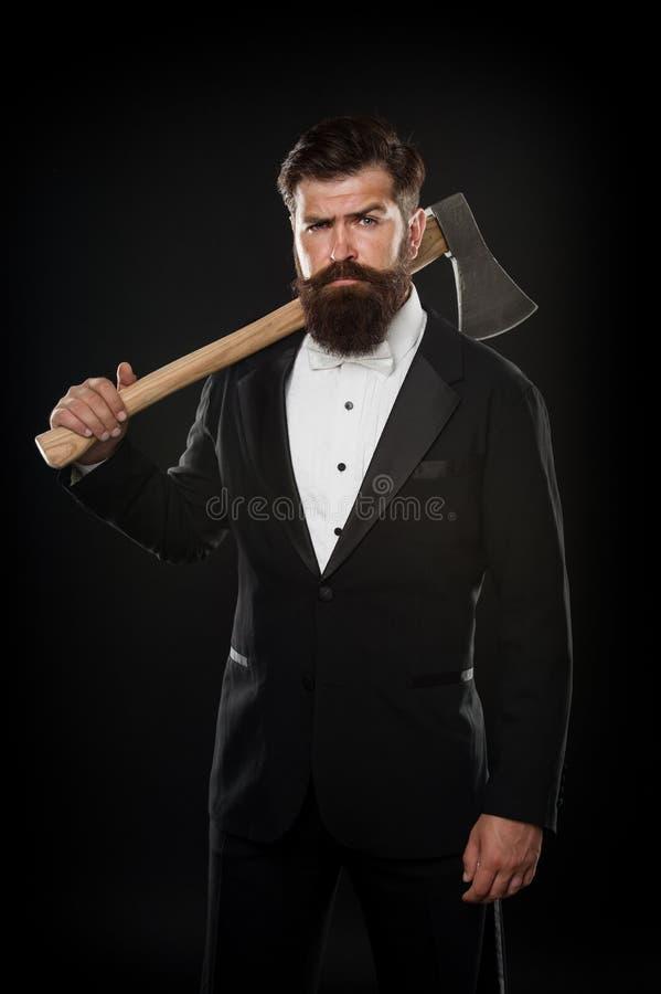 Responsabile del partito Tuxedo uomo brutale che ispira su sfondo nero scuro querela formale di un uomo d'affari sicuro barbiere  fotografia stock