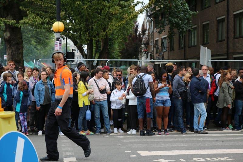 Responsabile di gruppo di carnevale di Notting Hill in servizio su una via del centro urbano durante l'evento speciale immagini stock libere da diritti