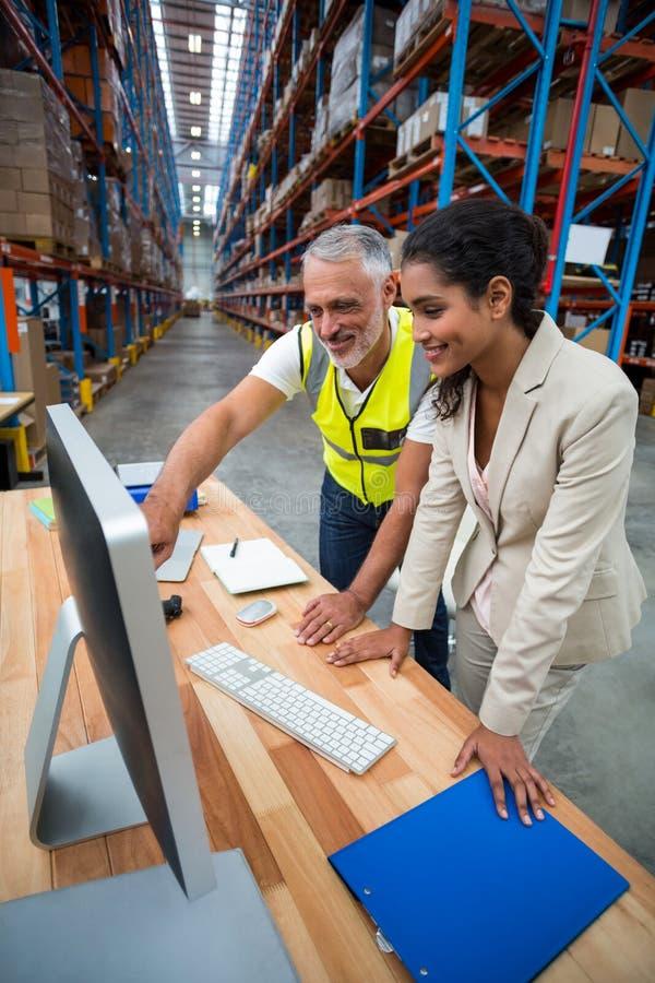 Responsabile e lavoratore del magazzino che discutono con il computer immagini stock libere da diritti