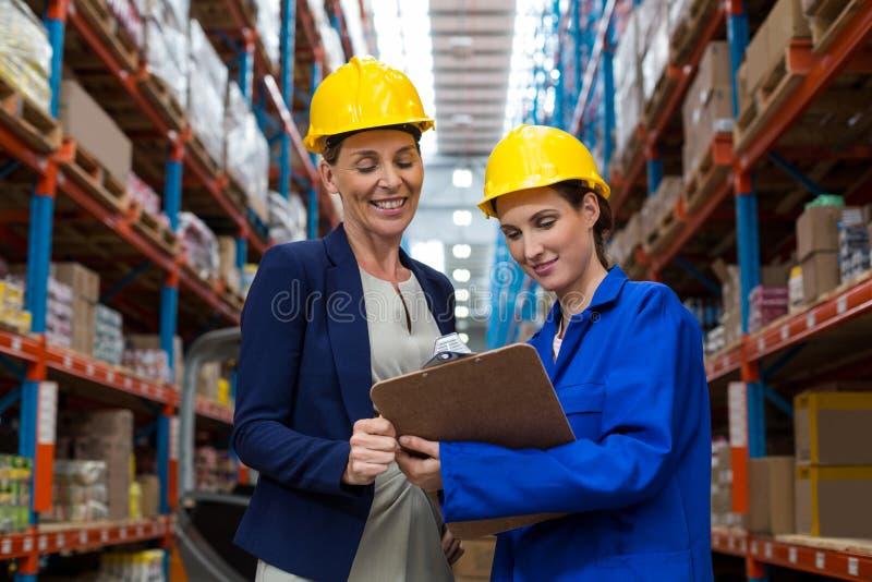 Responsabile e lavoratore del magazzino che discutono con la lavagna per appunti fotografia stock