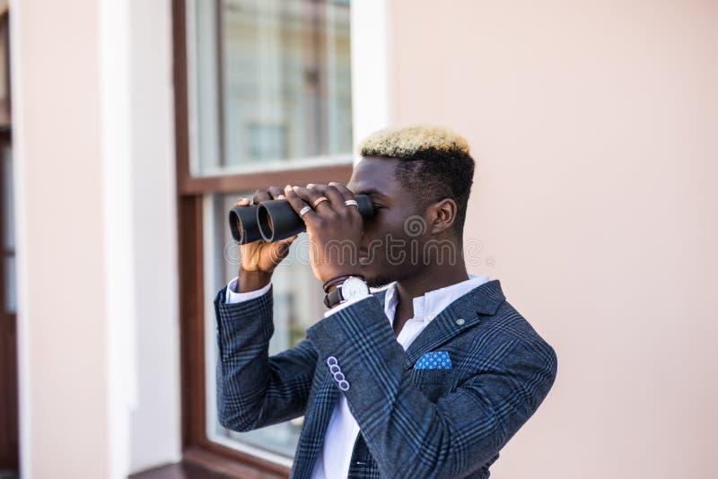 Responsabile elettrotecnico afroamericano facendo uso del binocolo che esamina sottostazione in ufficio fotografia stock libera da diritti