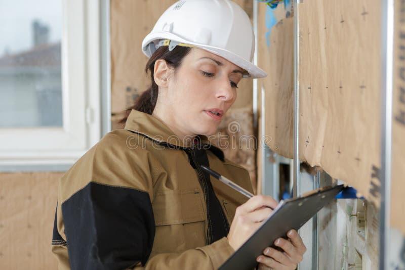 Responsabile femminile della costruzione che ispeziona i gessi sulla parete fotografia stock libera da diritti