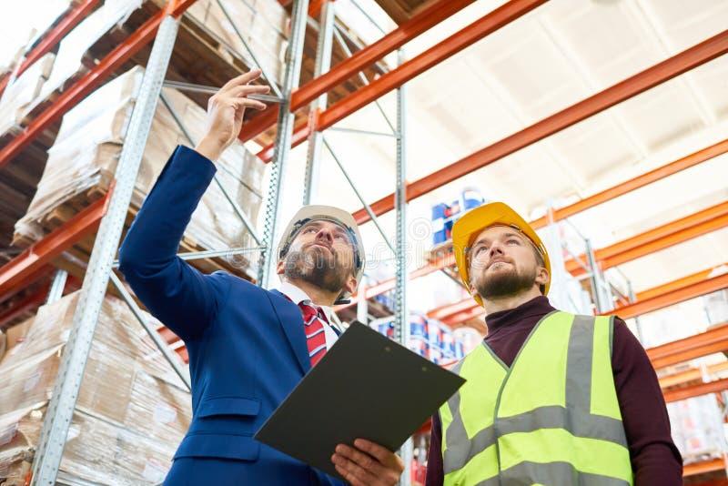 Responsabile Giving Instructions del magazzino al lavoratore immagine stock