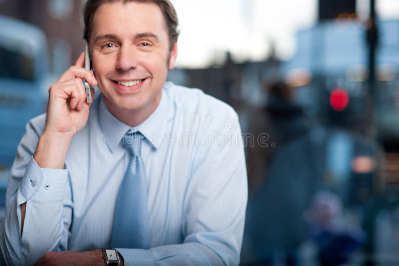 Responsabile maschio bello che per mezzo del suo telefono cellulare fotografia stock libera da diritti