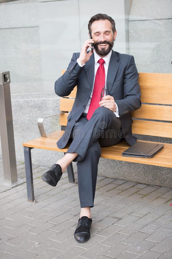 Responsabile sorridente che si siede sul banco e sulla telefonata Giovane ubicazione sorrisa bella dell'uomo d'affari sul banco c fotografie stock