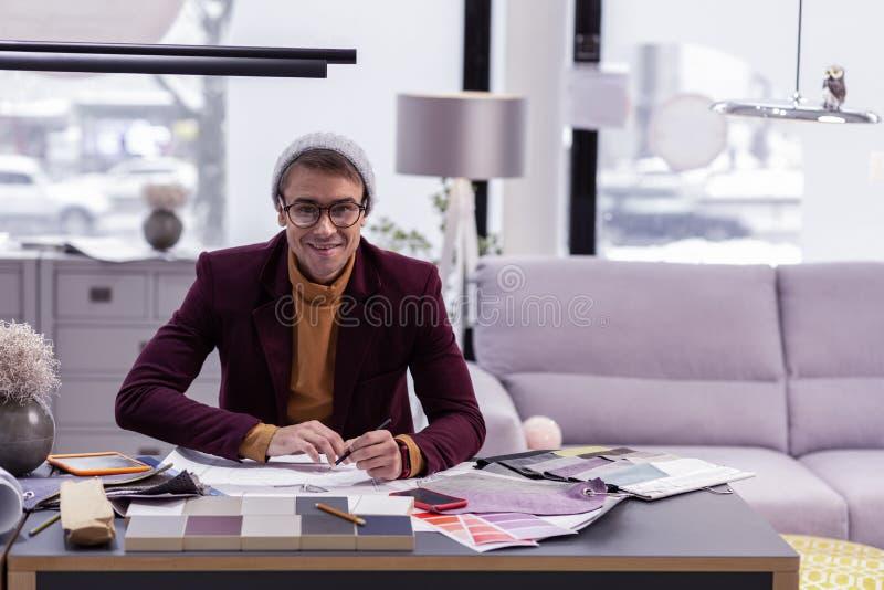 Responsabile vicenarian alla moda sorridente che lavora nell'ufficio ammobiliato moderno fotografia stock libera da diritti